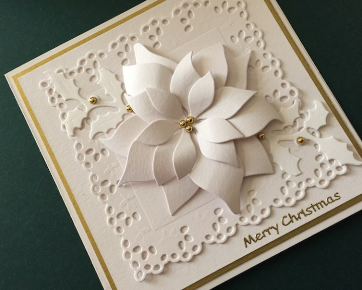 Hand made Christmas card with die cut poinsettia and holly
