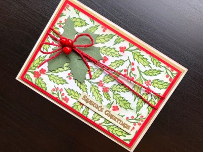 Christmas card with stamped layered holly background, die cut holly leaves and red jingle bells
