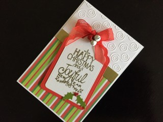 Hand made Christmas card with die cut tag shape, stamped and embossed greeting, ribbon and die cut holly