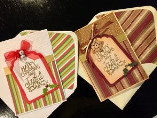 Two hand made Christmas cards with die cut tag shapes, heat embossed greeting and various embellishments