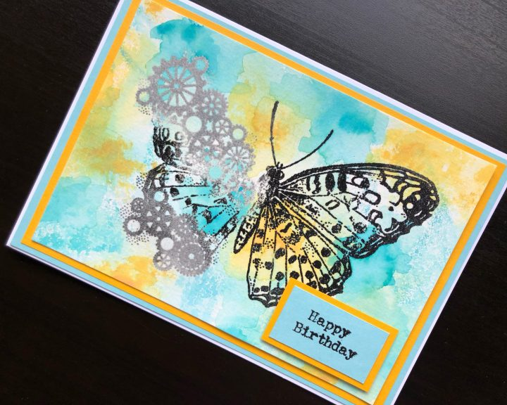 hand made birthday card with a heat embossed steampunk butterfly on an inked background