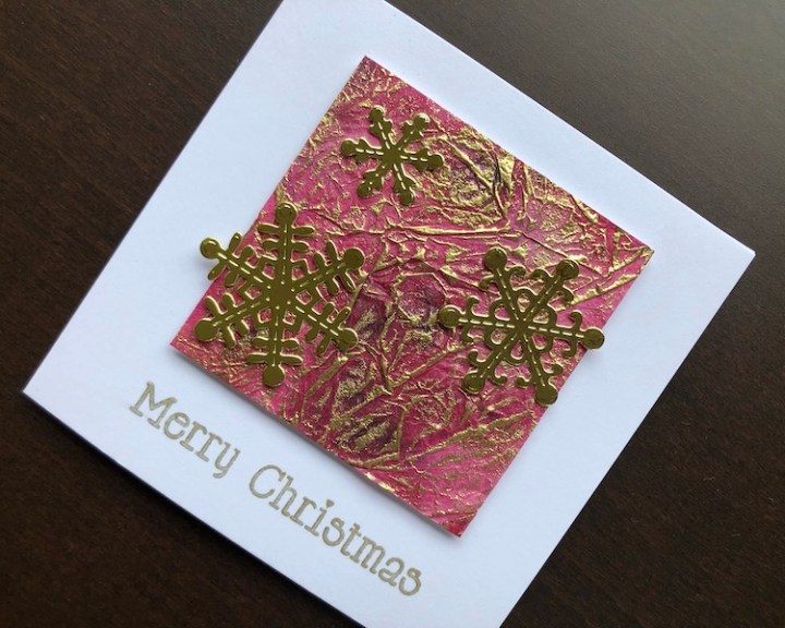 Hand made Christmas card with inked tissue panel and die cut snowflakes
