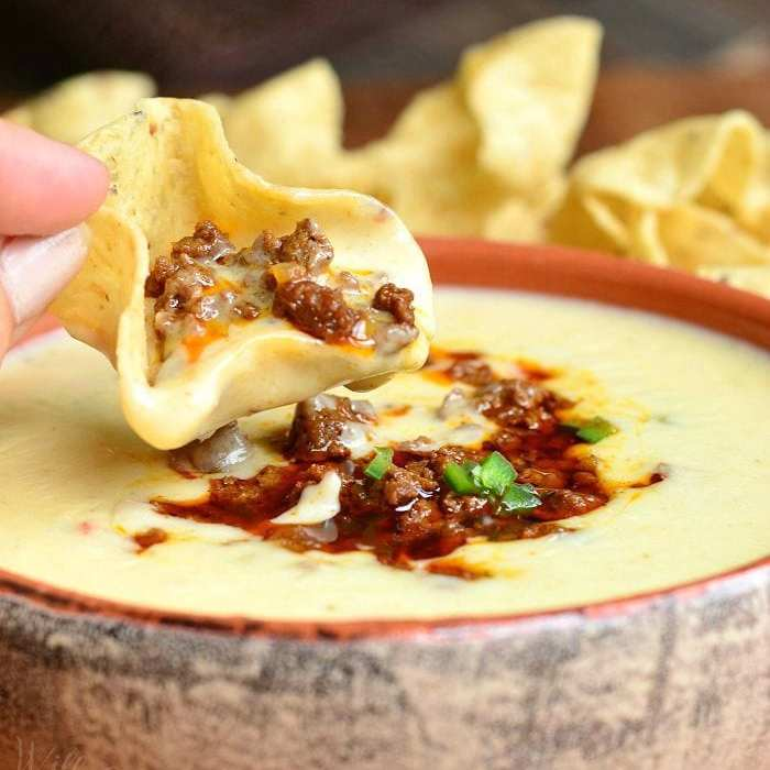 clay bowl filled with queso blanco dip and a hand holding one chip that was dipped into the dip