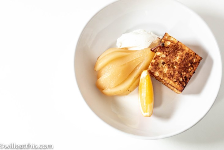 Sliced Citron Honey Tea Poached Pear with Toasted Pound Cake and orange served with yogurt on a white plate