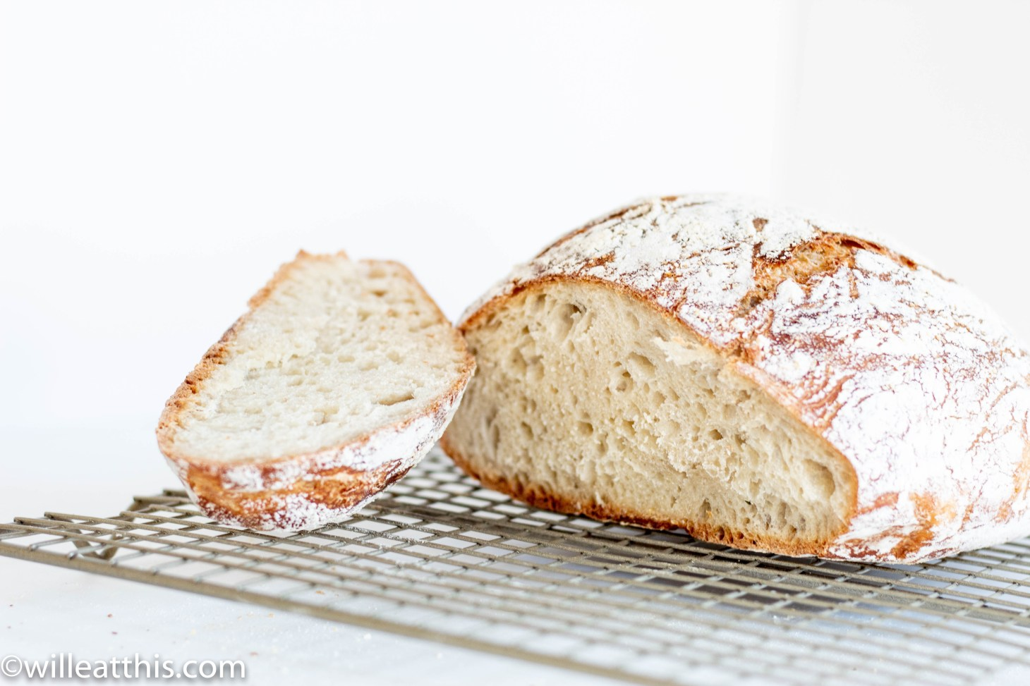 A loaf of knead bread with a slice beside it on a mesh rack