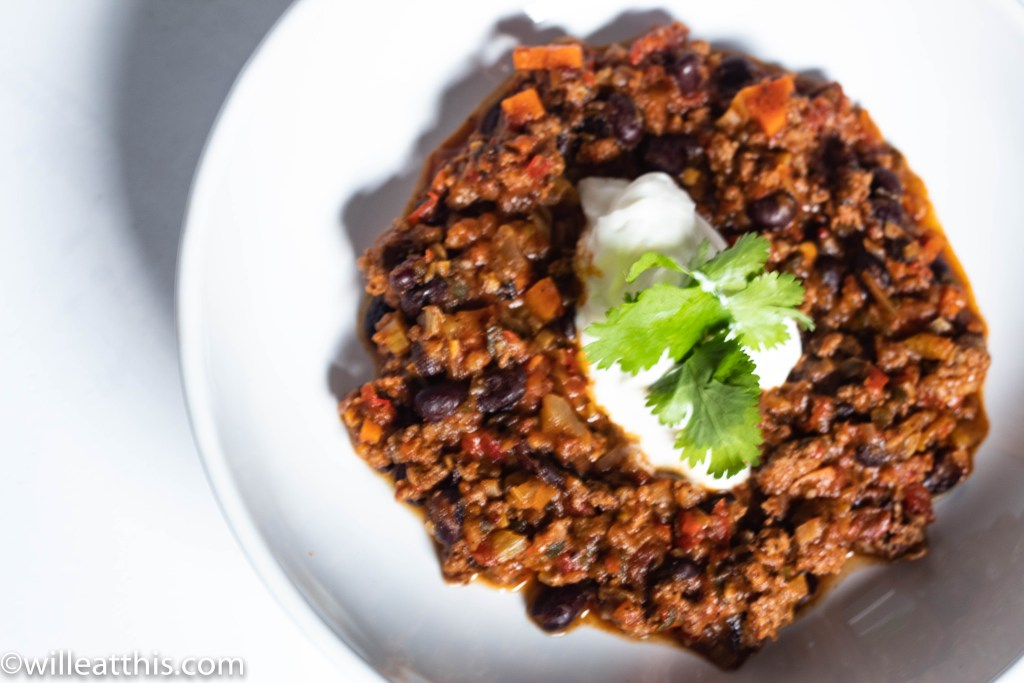 Chipotle Chili topped with yogurt and cilantro in a white shallow bowl