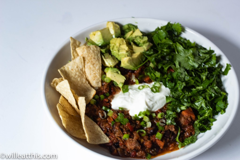 Chipotle Chili loaded with yogurt, cilantro, avocado, corn tortlla chips and spring onions