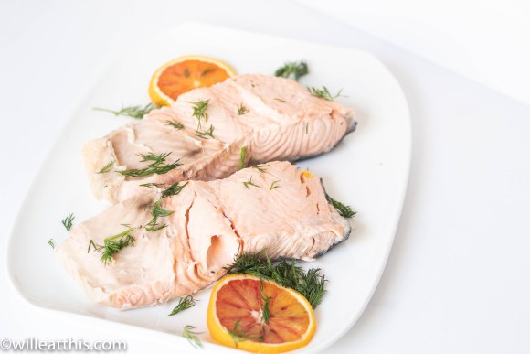 A pair of orange dill poached salmon on a plate with slices of orange and bits of dill