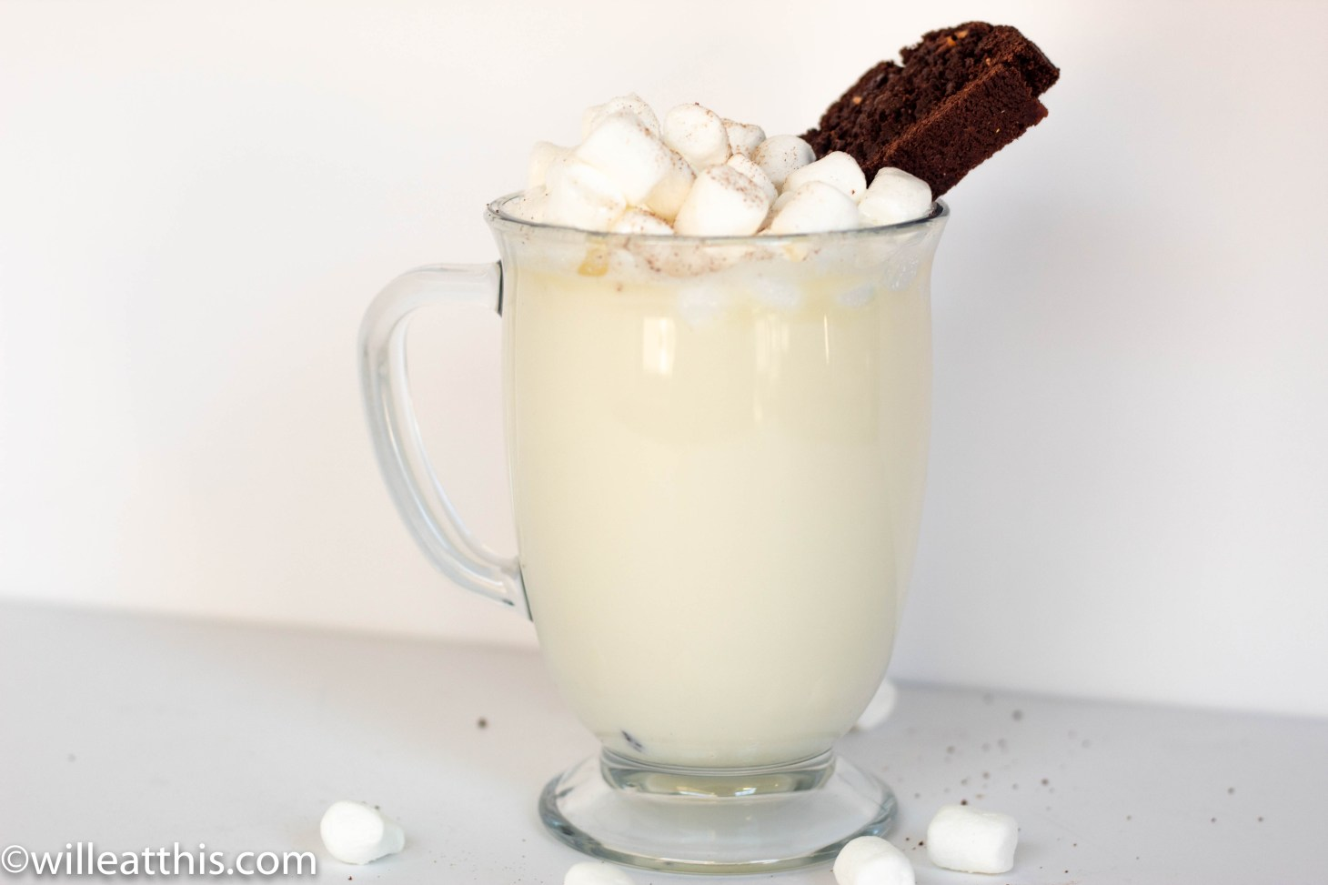 Hot white chocolate in a glass cup with marshmallow plus chocolate and grapefruit biscotti