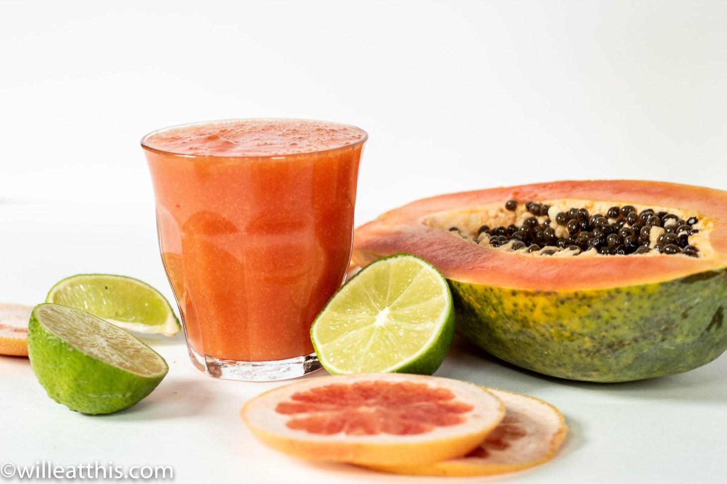 a glass of grapefruit papaya smoothie surrounded by cut citrus fruit and a half papaya