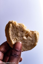 Holding a bitten walnut ginger shortbread between two fingers
