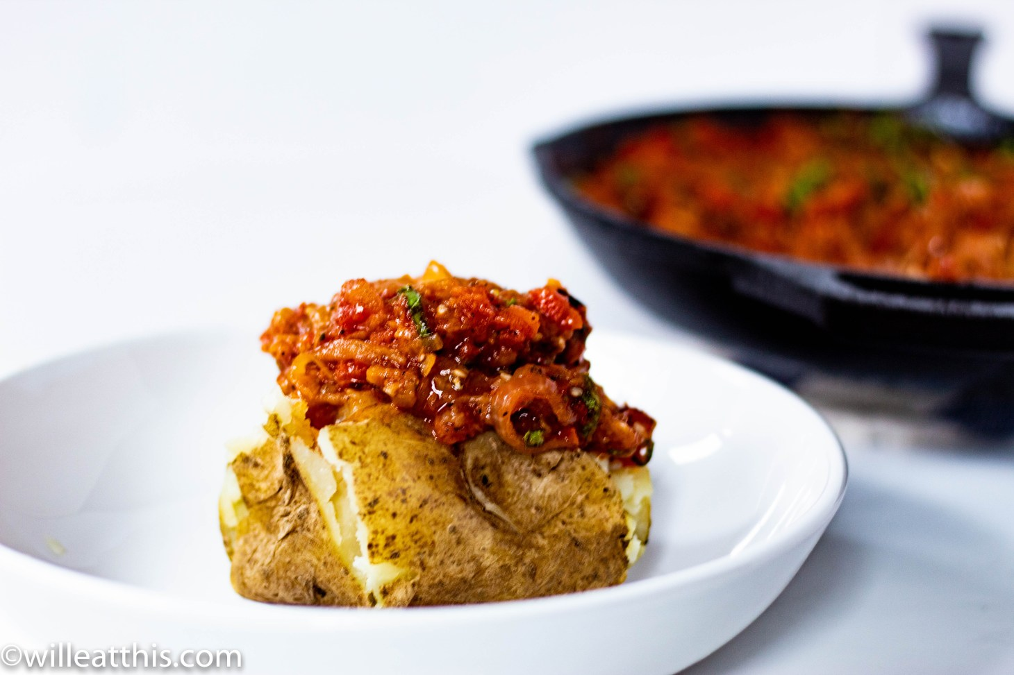 Baked potato on white plate served with tomato eggplant sauce