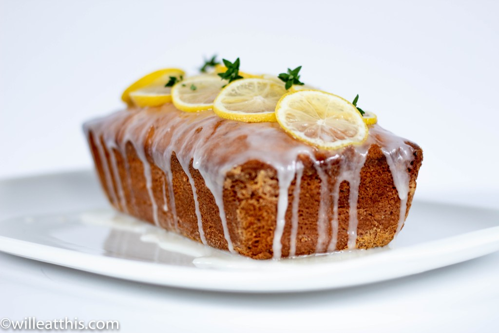 A loaf of lemon poppy seed cake decorated with slices of lemon and thyme buds with dripping frosting on a white plate