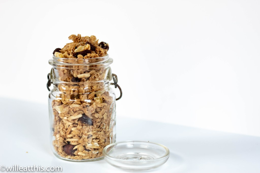 A glass jar filled with apple pie flavored granola clusters