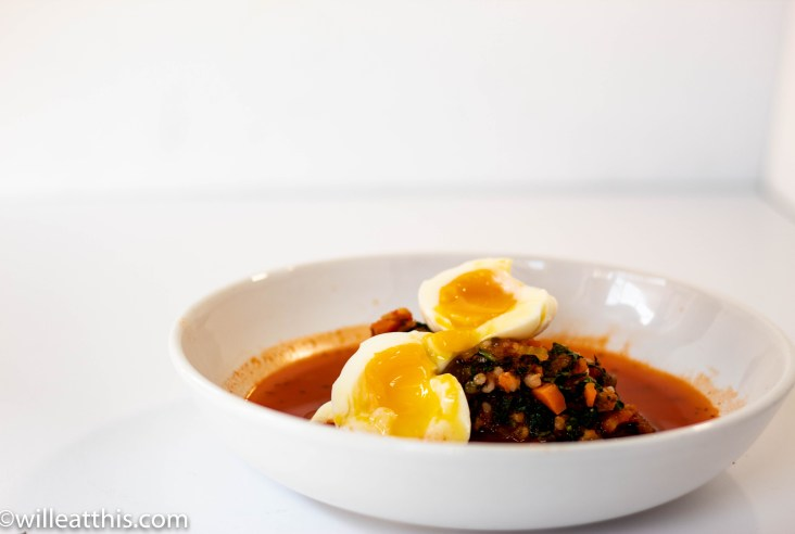 A white bowl filled with tomato chicken soup with kale. the soup is topped with a soft boiled egg.