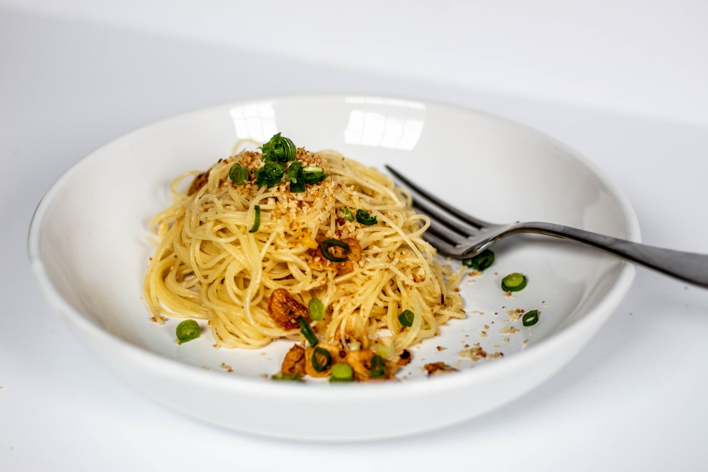 Spaghetti in Garlic Oil in a white plate dusted with breadcrumbs and spring onion slices