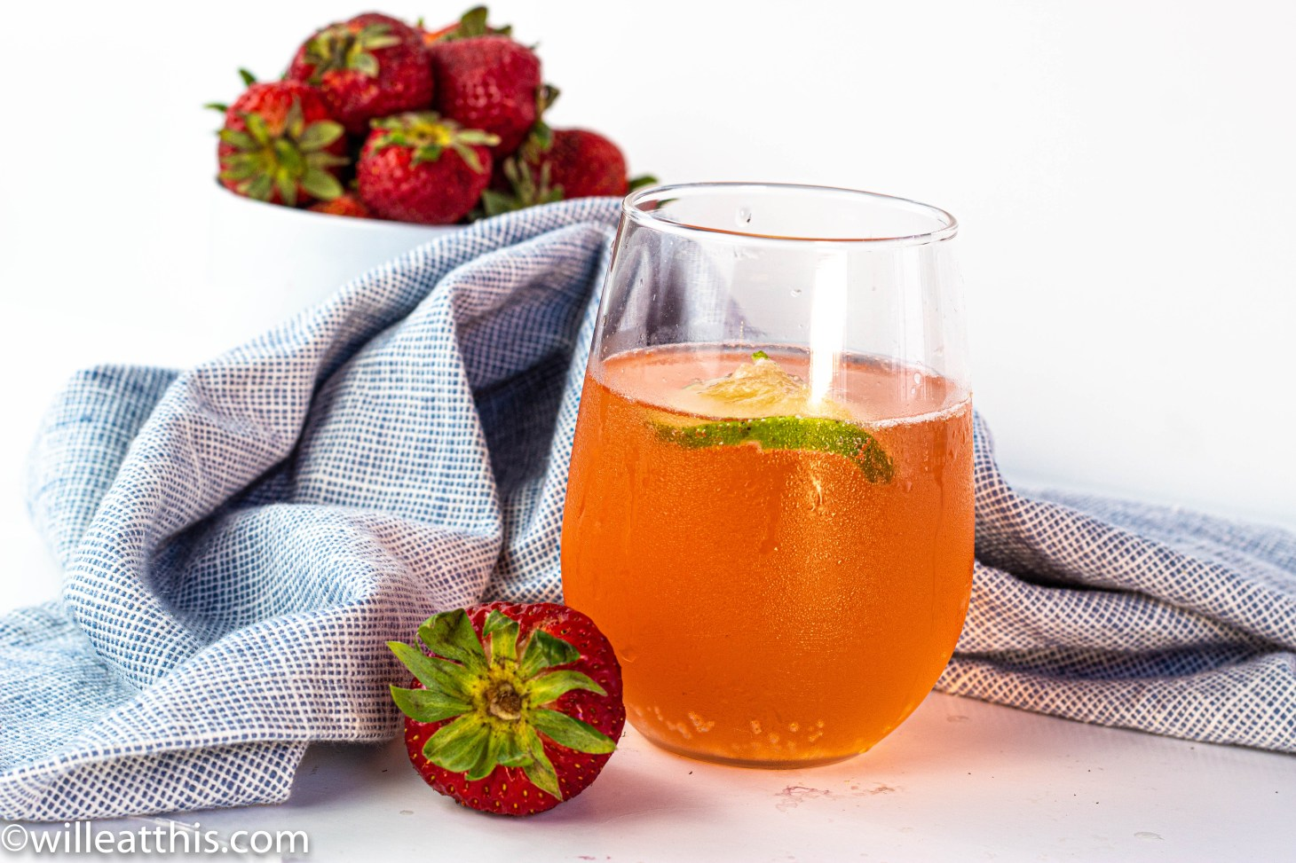A glass cup with sparkling strawberry and rhubarb drink. There is a folded blue napkin and strawberries in the background.