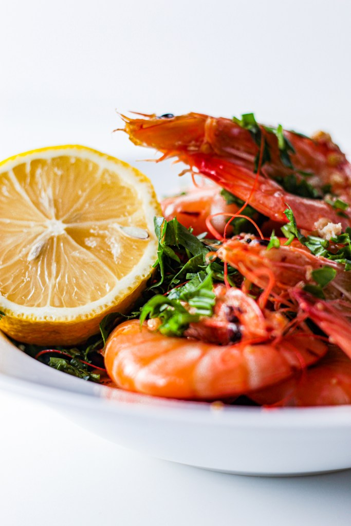 Cooked pink shrimp in lemon butter sauce dusted with chopped parsley leaves heaped in a white bowl. There is half a lemon on the side.