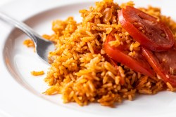 NIgerian jollof rice with sliced tomatoes on a white plate
