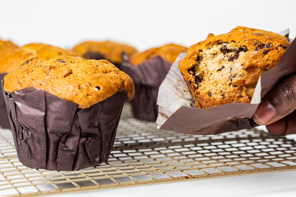 Baked chocolate chip buttermilk banana bread muffin on a rack cooling down