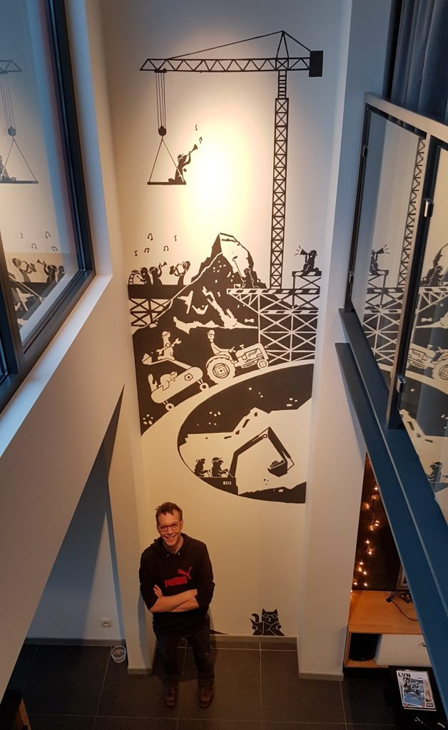 Willem Pirquin standing in front of the finished mural painting