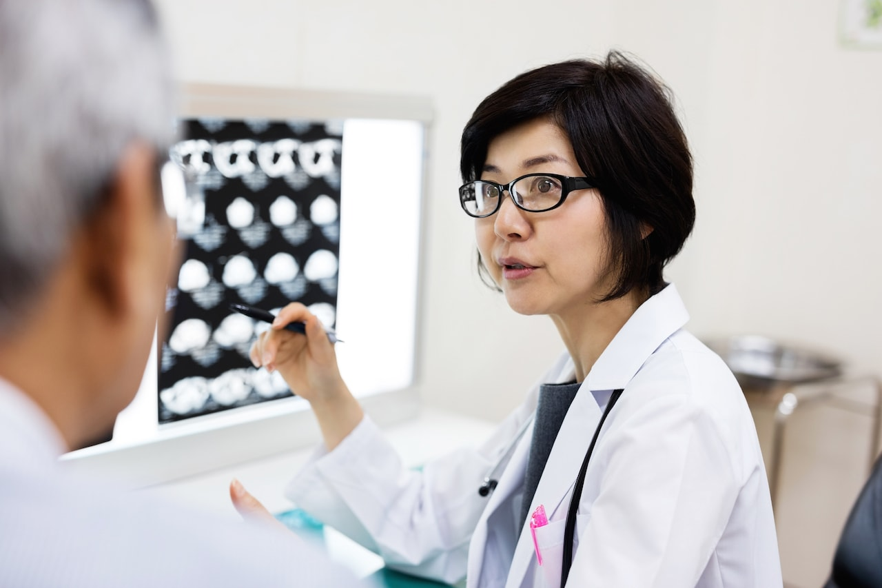Female doctor discussing with man over MRIs in hospital