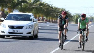 Two cyclists on a road and a white car