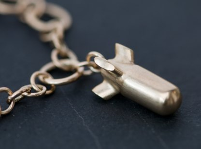 bomb charm on handmade gold chain bracelet