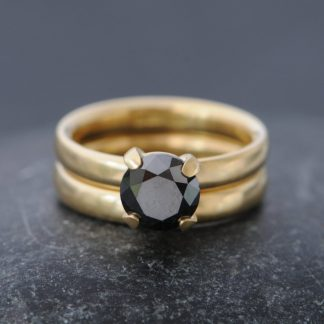 claw set black diamond solitaire in yellow gold engagement ring, with satin finish yellow gold wedding band