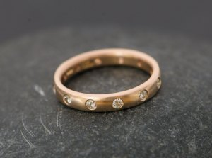 18k Rose Gold eternity band set with 12 small diamonds. Made by William White