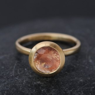 large peach Oregon Sunstone set in gold ring