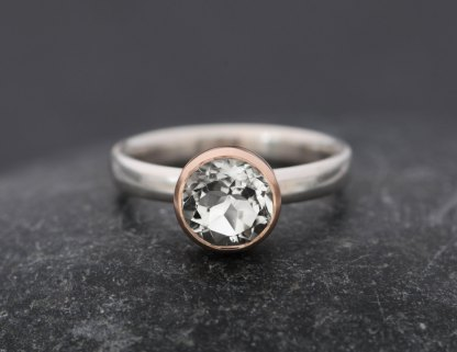 white topaz solitaire ring with gold bezel set in silver