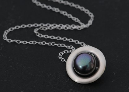 Large Peacock black pearl, set in a satin finished sterling silver halo design. Pearl is 11mm across. Designed and handmade by William White in Cornwall, UK