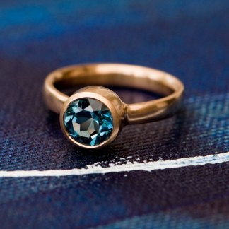 stunning blue topaz solitaire ring in rose gold