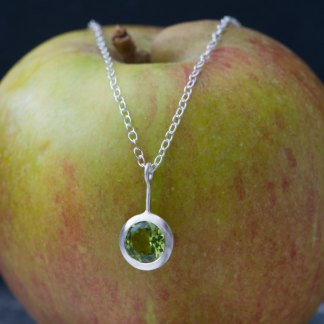 Peridot lollipop, set in satin finished sterling silver on a silver chain.