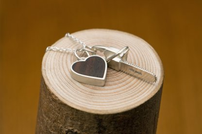Killer Charm necklace with Silver chainsaw & silver heart set with reclaimed rosewood, on a fine silver necklace. Designed and handmade by William White