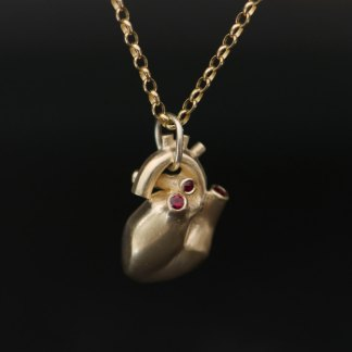 Anatomical heart necklace with 4 small rubies, set in 9K gold. Solid gold heart on a medium weight 9K gold chain. Designed & handmade by William White