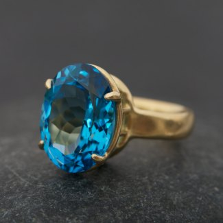 bright blue swiss blue topaz stone claw set in gold ring