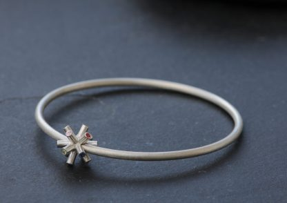Particle collision bangle with sapphires in silver