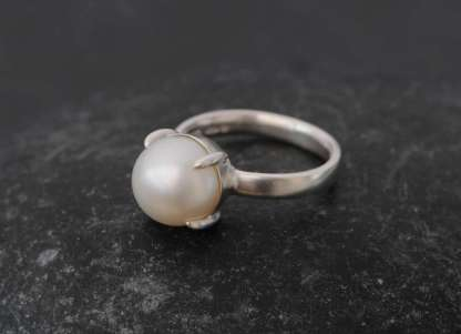 White pearl claw set into silver ring