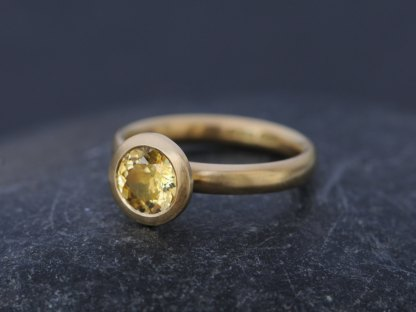 Yellow Sapphire set in 18K gold ring, seen from the side on a dark background