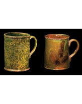 "9ETWO NEW ENGLAND REDWARE ALE MUGSCylindrical shape with double coggle line defined lip and multiple reeded lines (seven) below the applied handle, tooled footed base, mottled dark green on a light green background inside and out, one side shows a triangular piece at the top glued and a crack down the body, intact and stable, 5 3/4"" h, 4"" dia; Cylindrical shaped mug with slight flare at double coggle lined lip, finely shaped applied handle, double coggle line at midpoint, tooled foot, dark green glaze with light green and manganese brown swatches, light brown glazed interior, very minor imperfections, overall good condition, 5"" h, 4"" dia (at lip), (ex. Curry collection).$600-800"