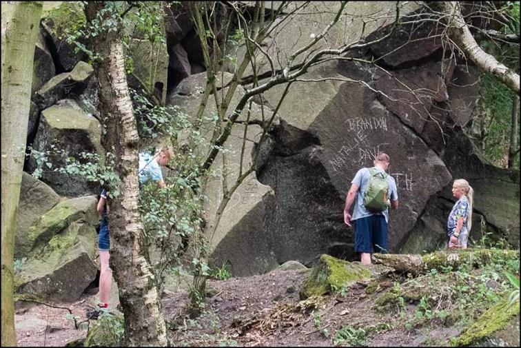 Parents with children vandalising the rock