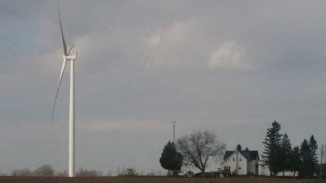 3-MW wind turbine and house near Brinston, south of Ottawa. Ontario's guidelines were set with reference to WHO guidelines which are not adequate for wind turbine noise. [Photo: Ray Pilon, Ottawa]