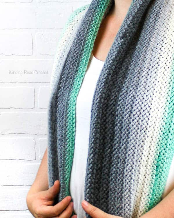 The Herringbone Inifintiy Shawl is a great crochet shawl to carry with you. This free crochet pattern is great for beginners that are ready to try a new stitch. I have a herringbone crochet stitch photo tutorial. The texture in this shawl is very unique and the shawl can be worn like a thick infinity scarf. #crochet #crochetpattern #forbeginners #easy #shawl #crochetshawl #inifinityscarf