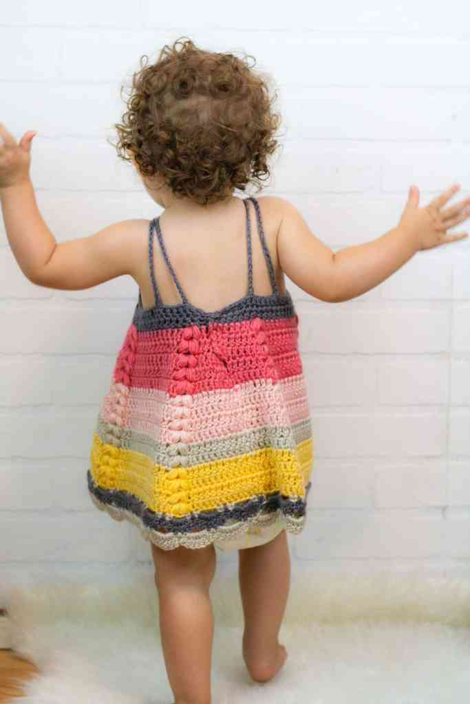 Crochet a beautiful toddler baby dress. This dress has a simple shape with some beautiful extra details. Free crochet pattern by Winding Road Crochet. #crochetbabydress #crochettoddlerdress #toddlerdress #freecrochetpattern