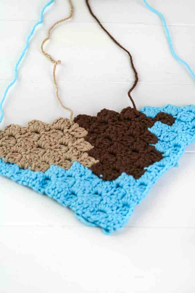 Crochet a quick and easy acorn c2c crochet graph. The graph is the perfect size for a pot holder or washcloth. Free pattern by Winding Road Crochet.