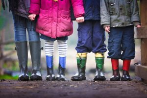 A group of four children lined up wearing outdoor clothes and wellington boots