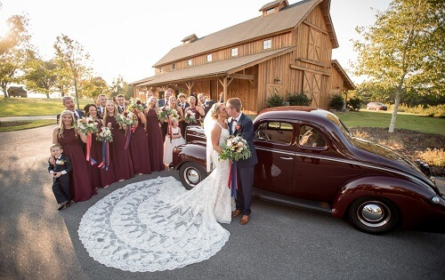 Bride and groom kissing next to antique car near bridal party standing in front of Windy Hill Wedding & Event Barn