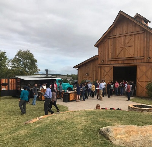 Windy Hill Event barn with crowd of people spilling out of open doors next to a food truck
